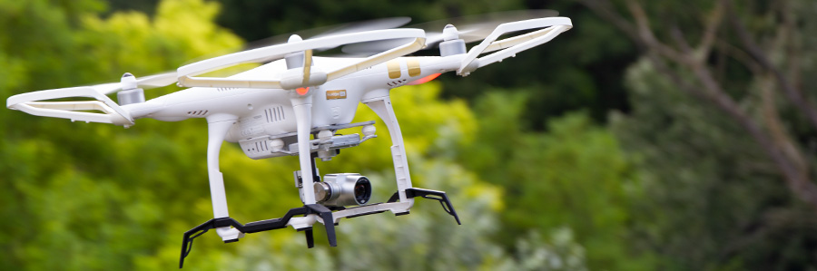 close shot of drone flying in wooded area